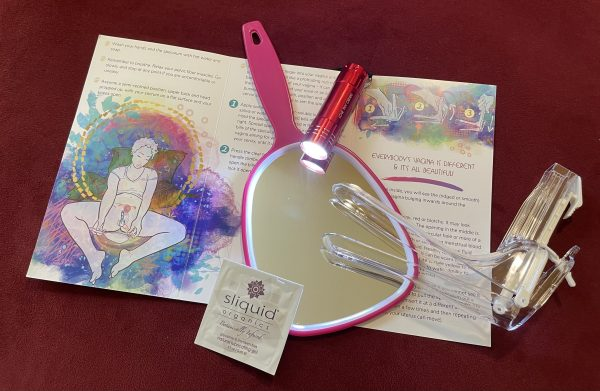 Pamplhet with magenta mirror, clear speculum, lube packet, flashlight on top